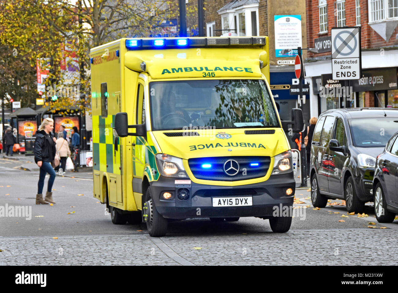 East of England Emergency Ambulance Service NHS vehicle & crew on 999 journey along Brentwood Essex with shoppers - Stock Image
