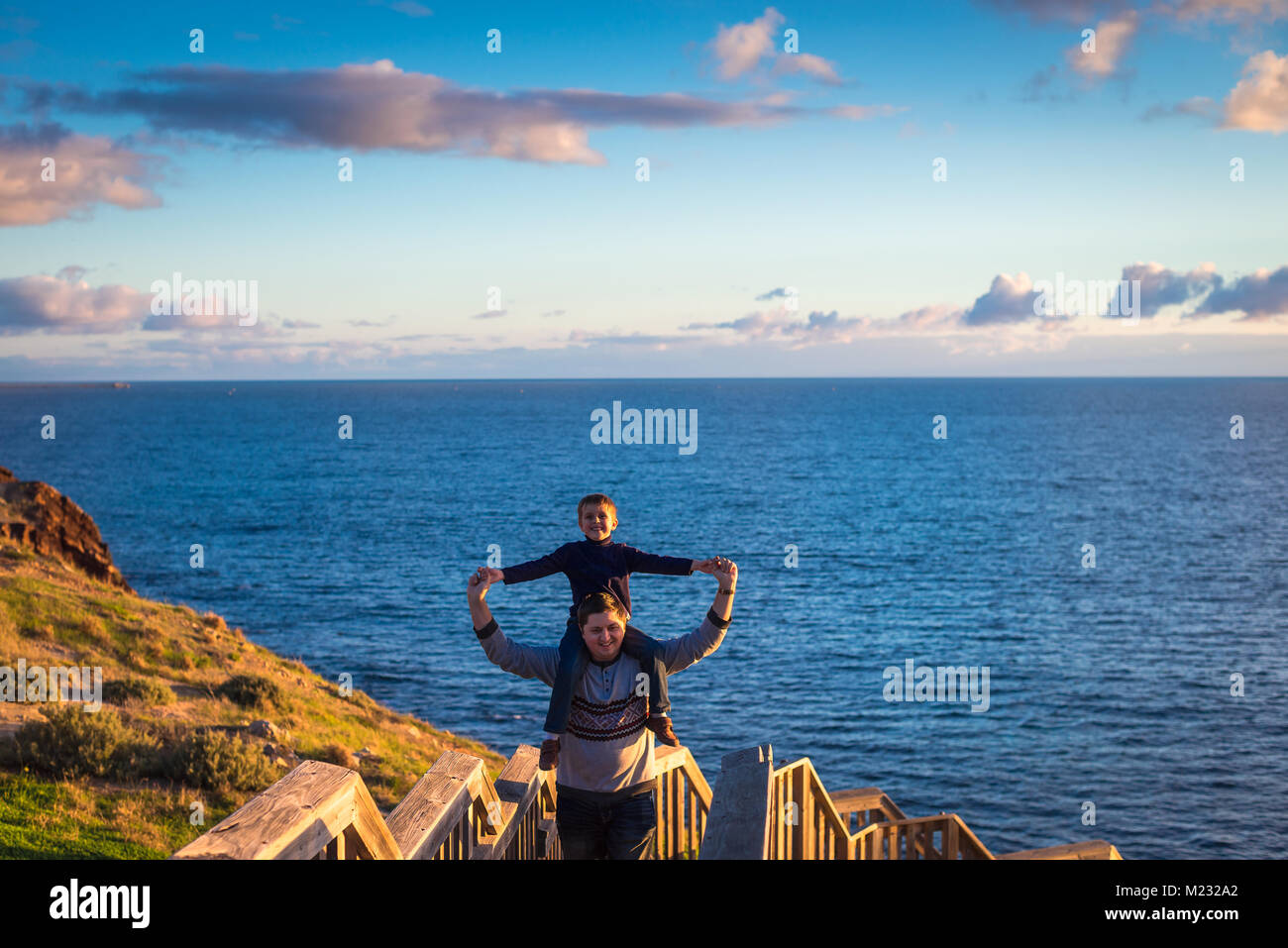Father giving his son piggyback ride at Hallett Cove boarwalk while enjoying sunset, South Australia - Stock Image
