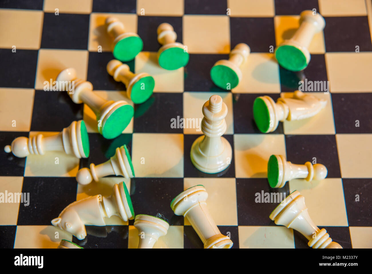Chess: King in the middle of fallen pieces on chess board. - Stock Image