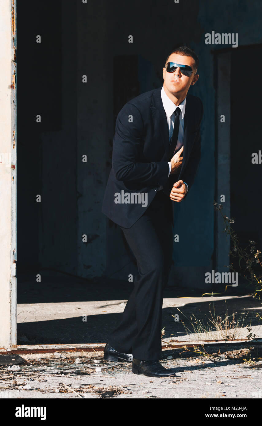 Handsome man in black suit and sunglasses. Secret agent, mafia, bodyguard concept. - Stock Image