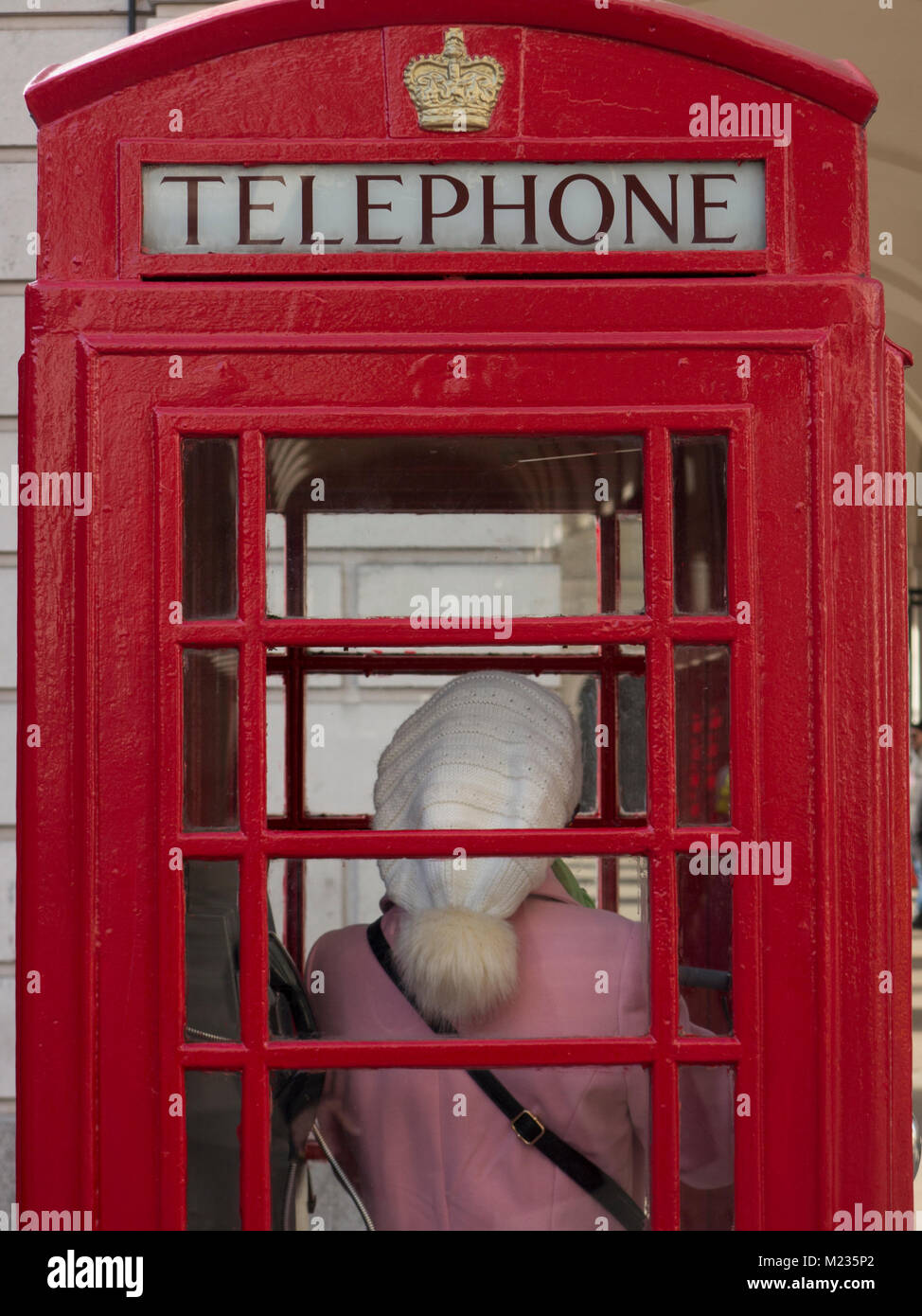 A woman on the phone in a London telephone box wearing a pink coat and a bobble bat - Stock Image