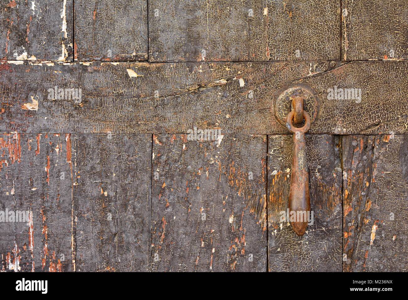 Close-up of worn out shabby wooden door with rusty metal doorbell - Stock Image