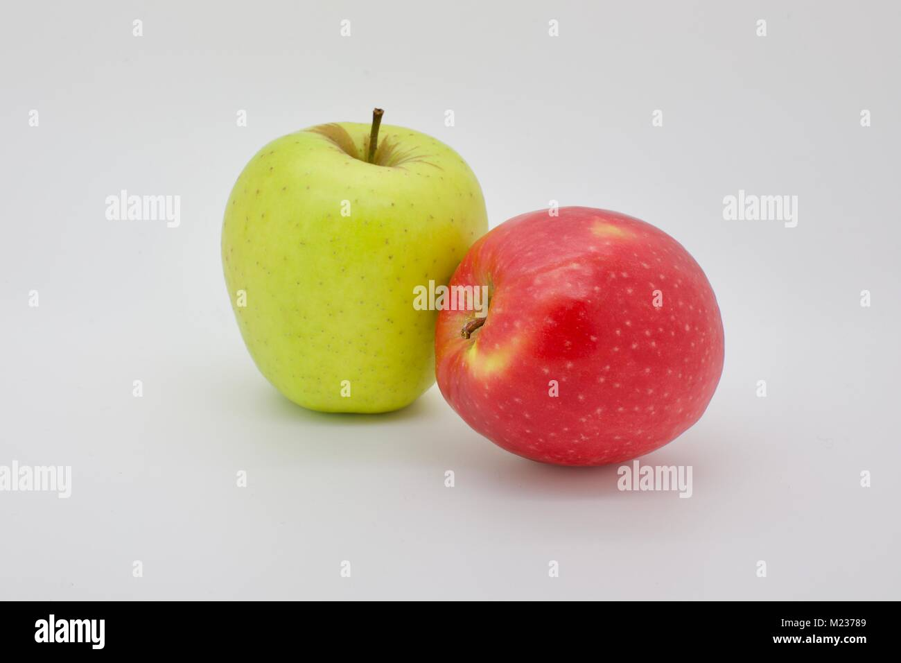 Two varieties of apples one Golden Delicious and a rosy red Jazz apple on a white background - Stock Image