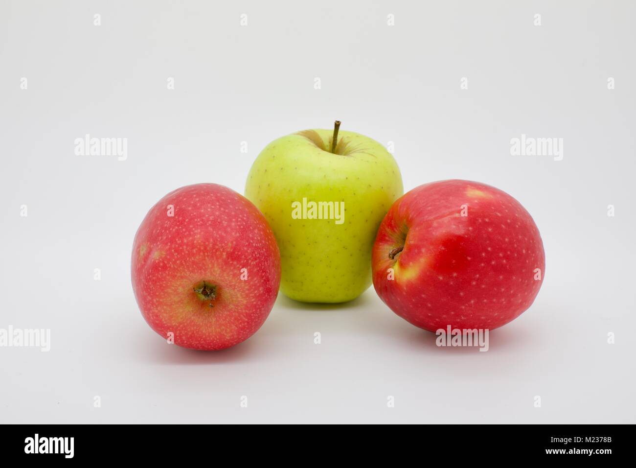 Two rosy red Jazz apples and a Golden Delicious apple in the middle on a white background - Stock Image