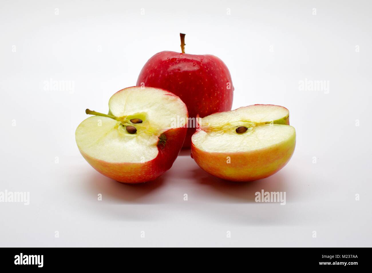 Two Jazz apple with one sliced in half on a white background - Stock Image