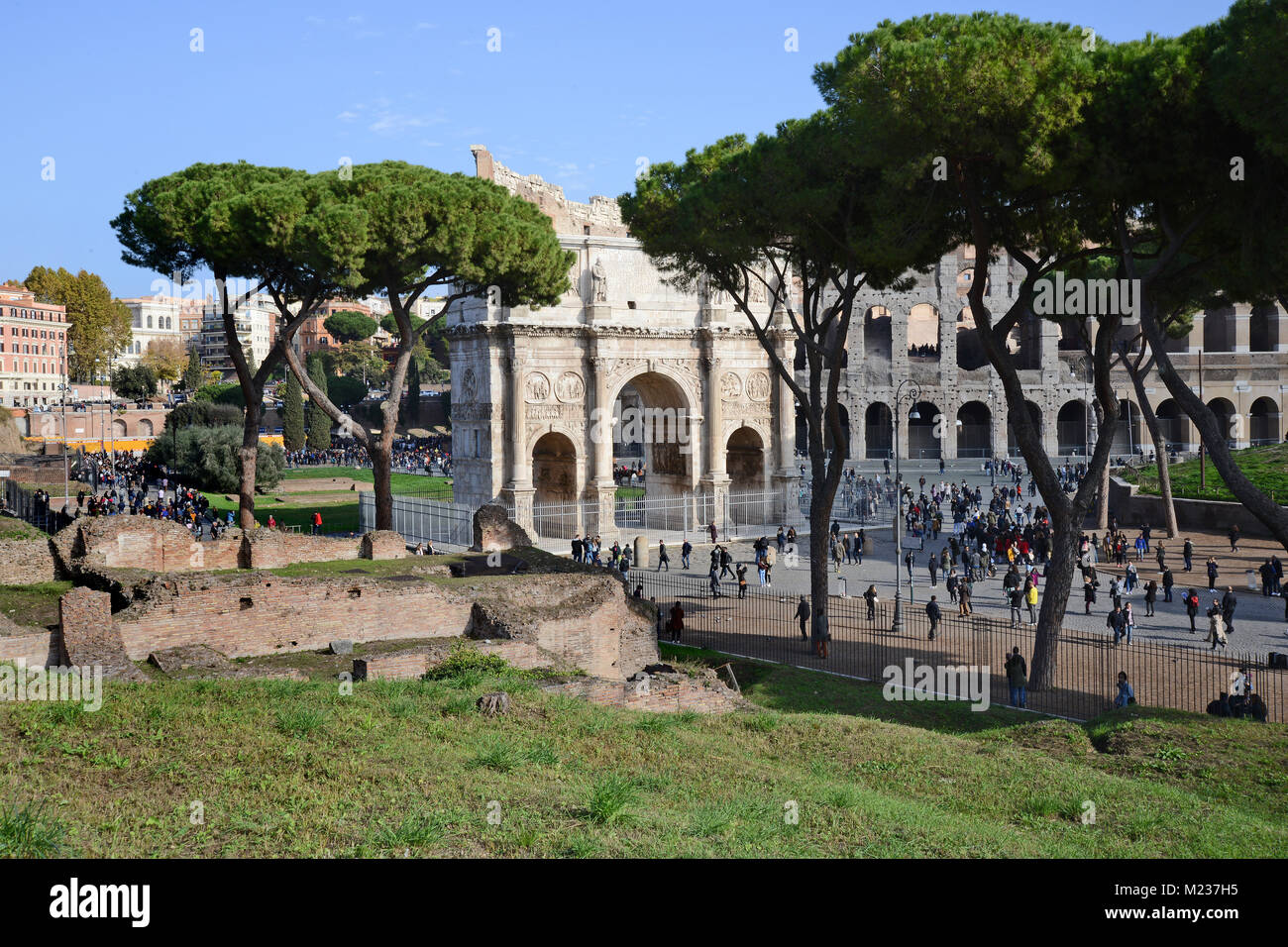 The Archway of Constantine with the Colosseum behind with crowds of tourists surrounding it, seen from the lower - Stock Image