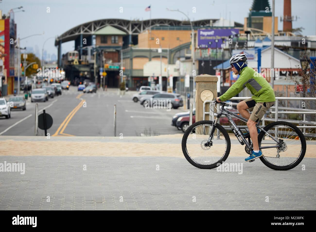 New York city  Coney Island–Stillwell Avenue Subway terminal in Brooklyn, cycling bike cyclist  on the beach promenade Stock Photo