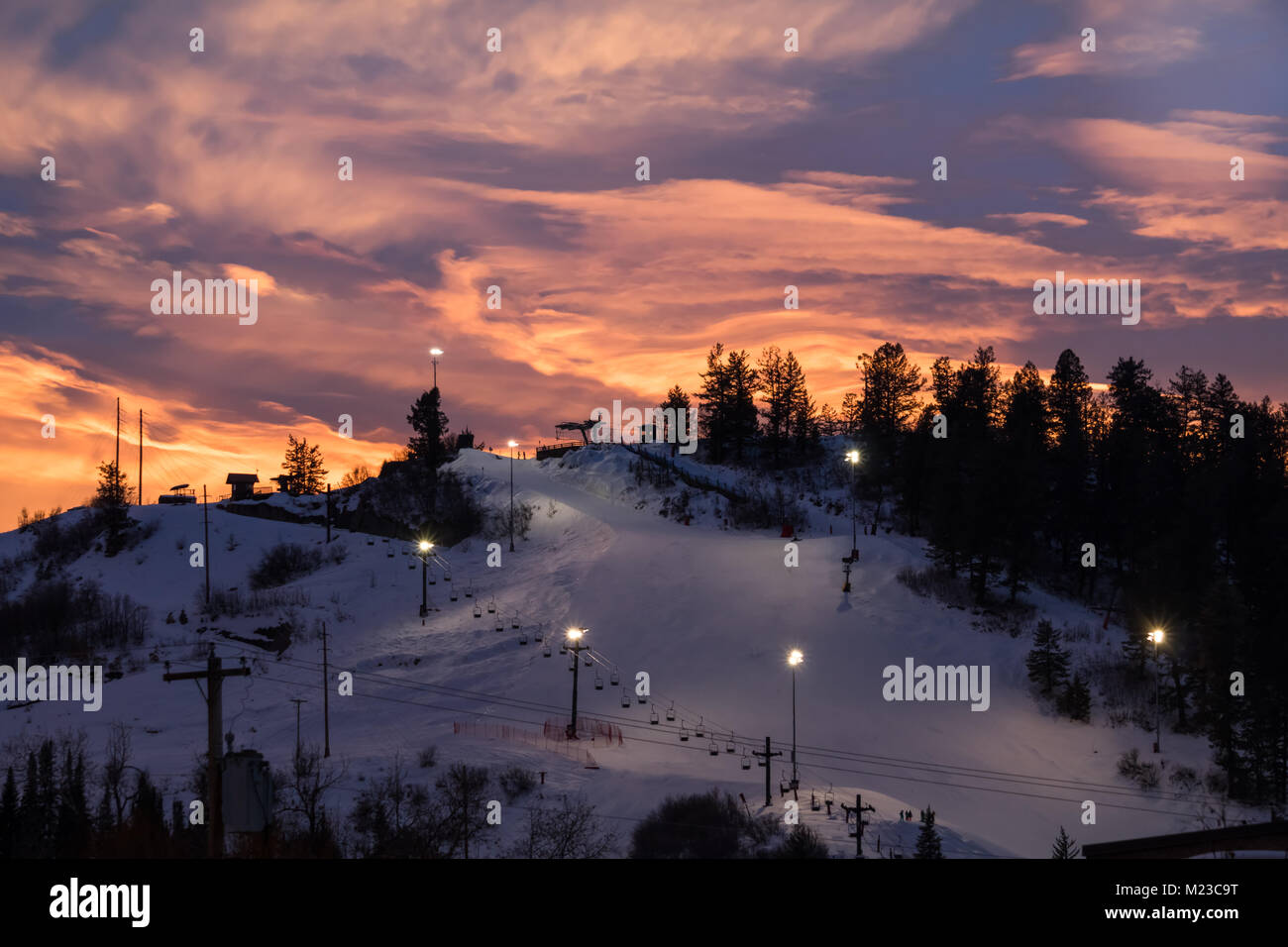 View of of a ski slope lit for night skiing in Steamboat Springs, Colorado; after sunset; colorful sky in the background - Stock Image