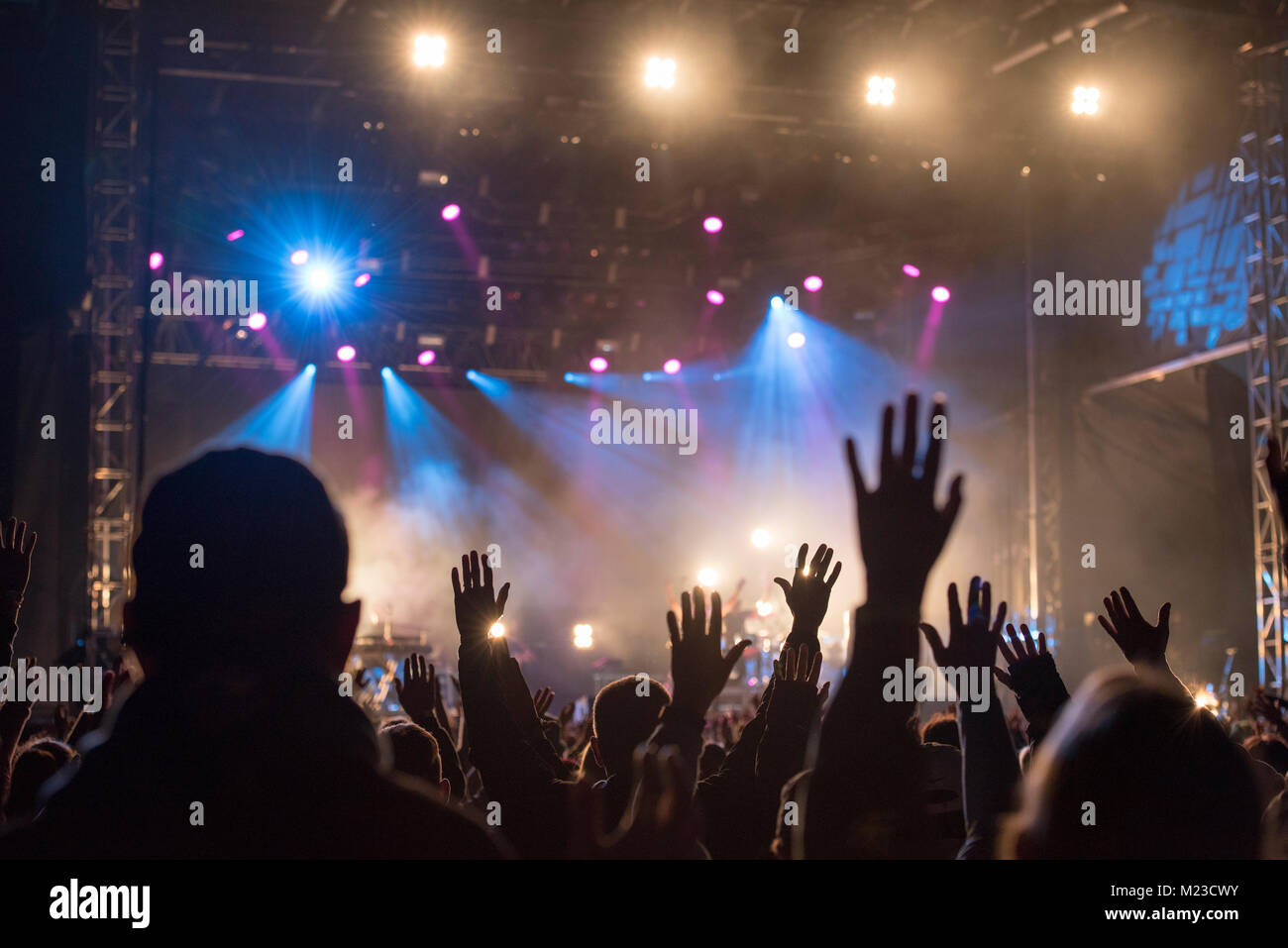Christians raising their hands in praise and worship at a night music concert - Stock Image