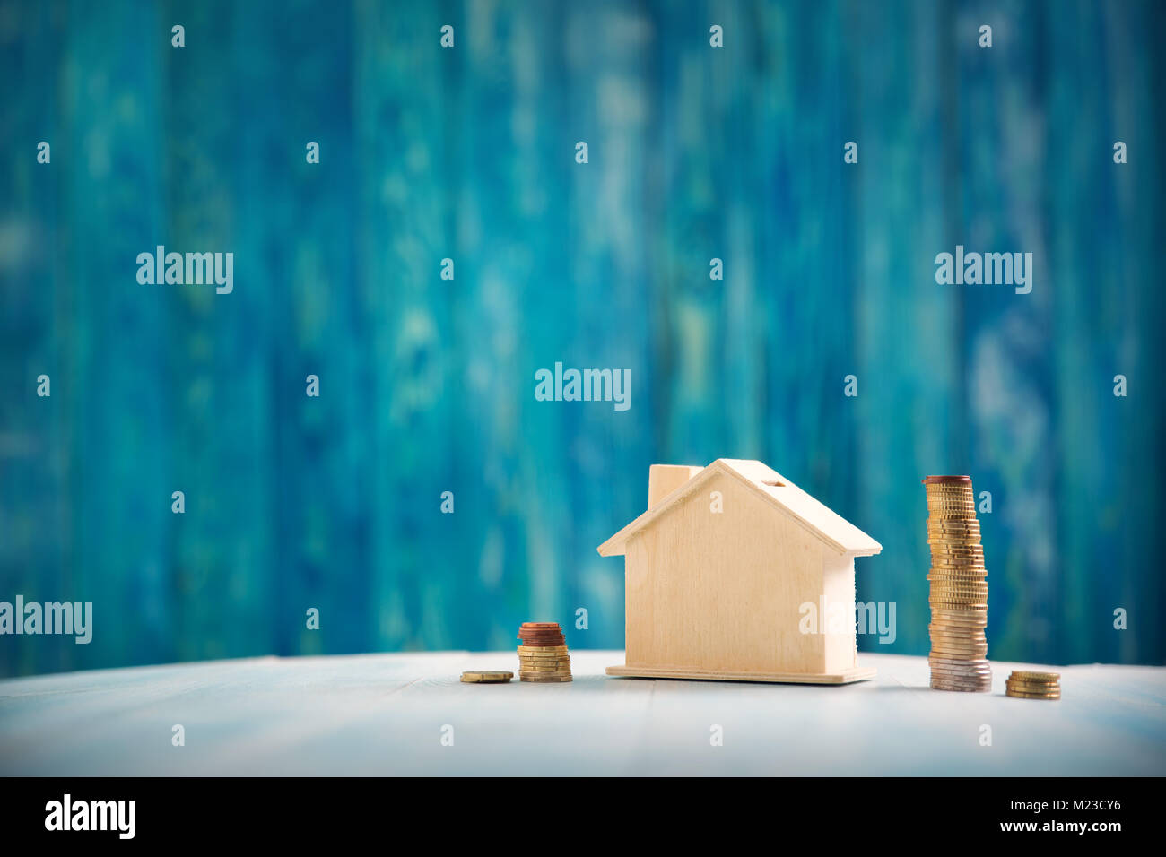 Red house on wooden background with banknotes - Stock Image