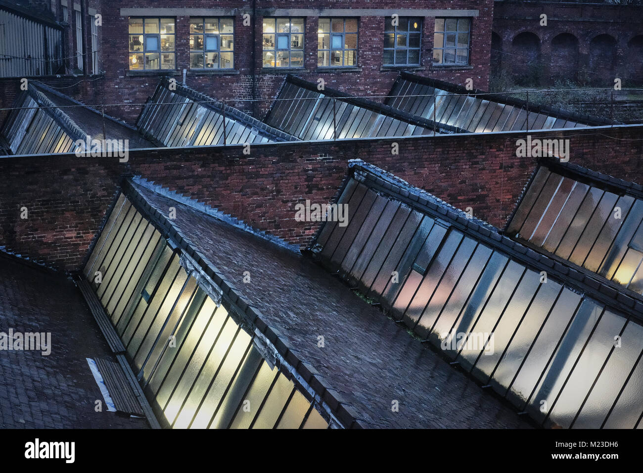 Dusk over a wet roofline of a factory in northern England. Roof tiles, brick and window glass are seen with light - Stock Image