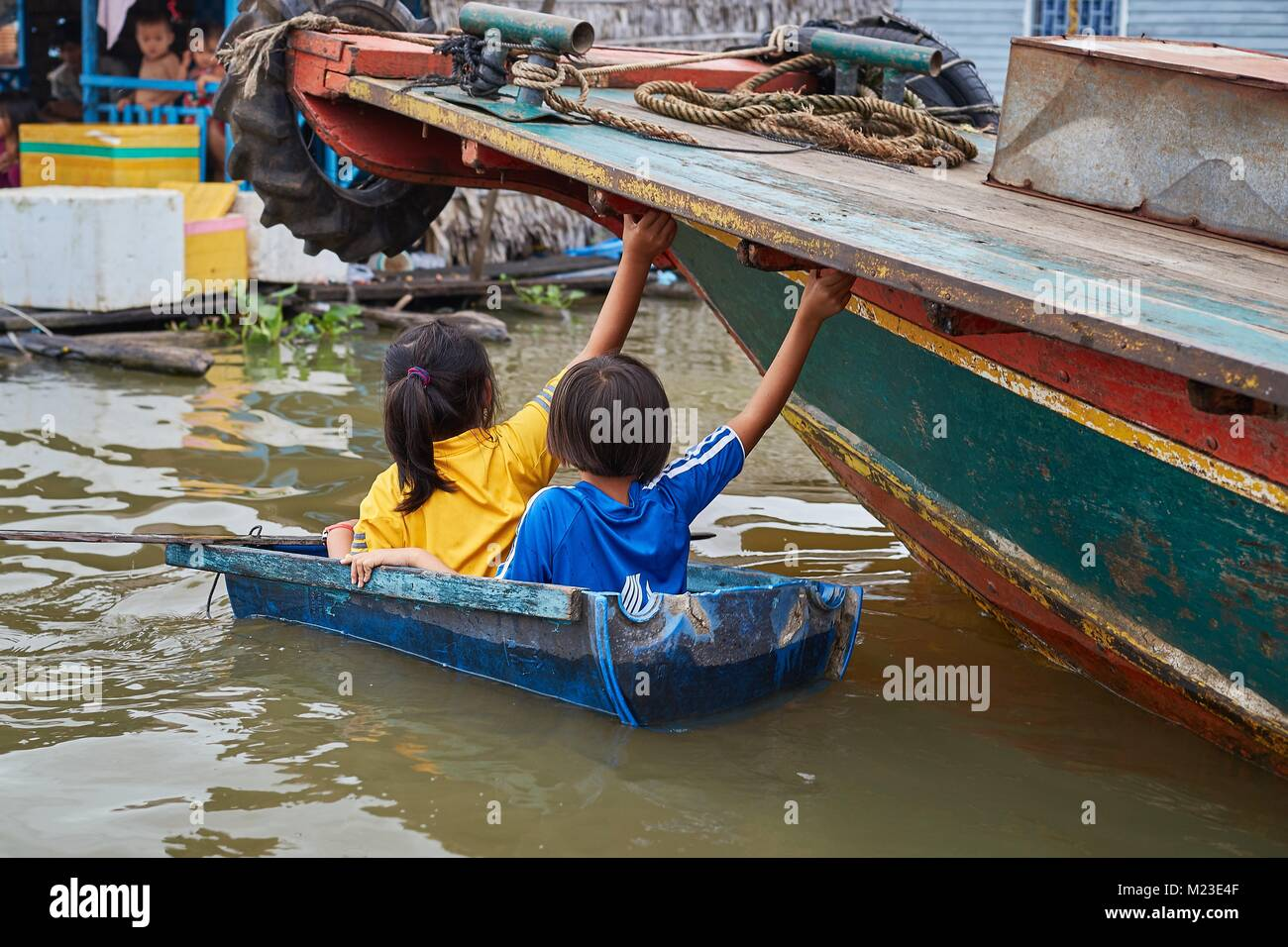 Children rowing on jerrican, Kompong Chhnang, Cambodia - Stock Image