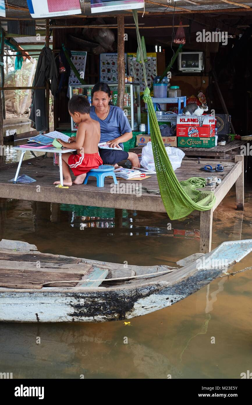 Little boy doing shool homework with his mother in House on stilts, Kompong Chhnang, Cambodia Stock Photo