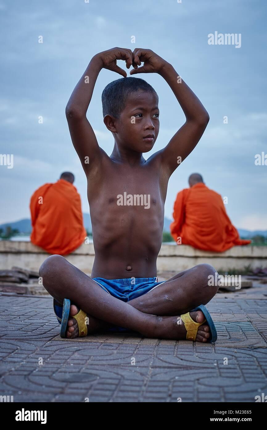 Cambodian boy posing behind monks, Kompong Chhnang, Cambodia - Stock Image