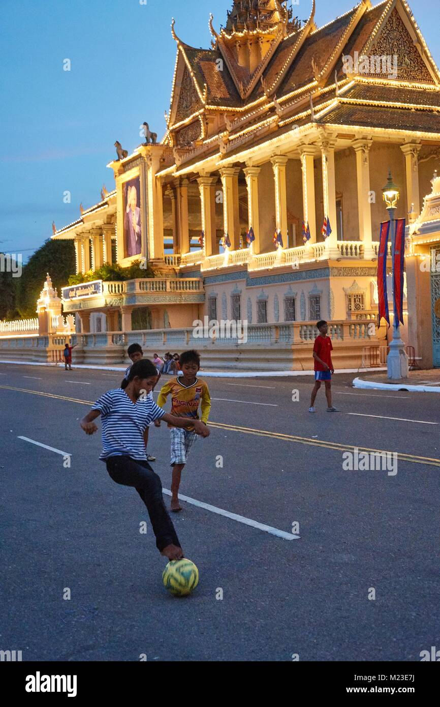 Cambodian girl and Children on floating house, Kompong Chhnang, Cambodia playing football in front of Royal Palace, Stock Photo