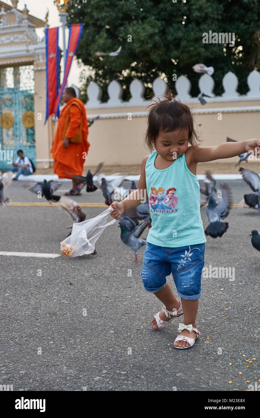 Little girl feeding birds (pigeon) in front of Royal Palace, Phnom Penh, Cambodia - Stock Image