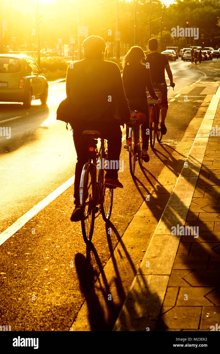 Bicyclists in a line ride a street against sun - Stock Image
