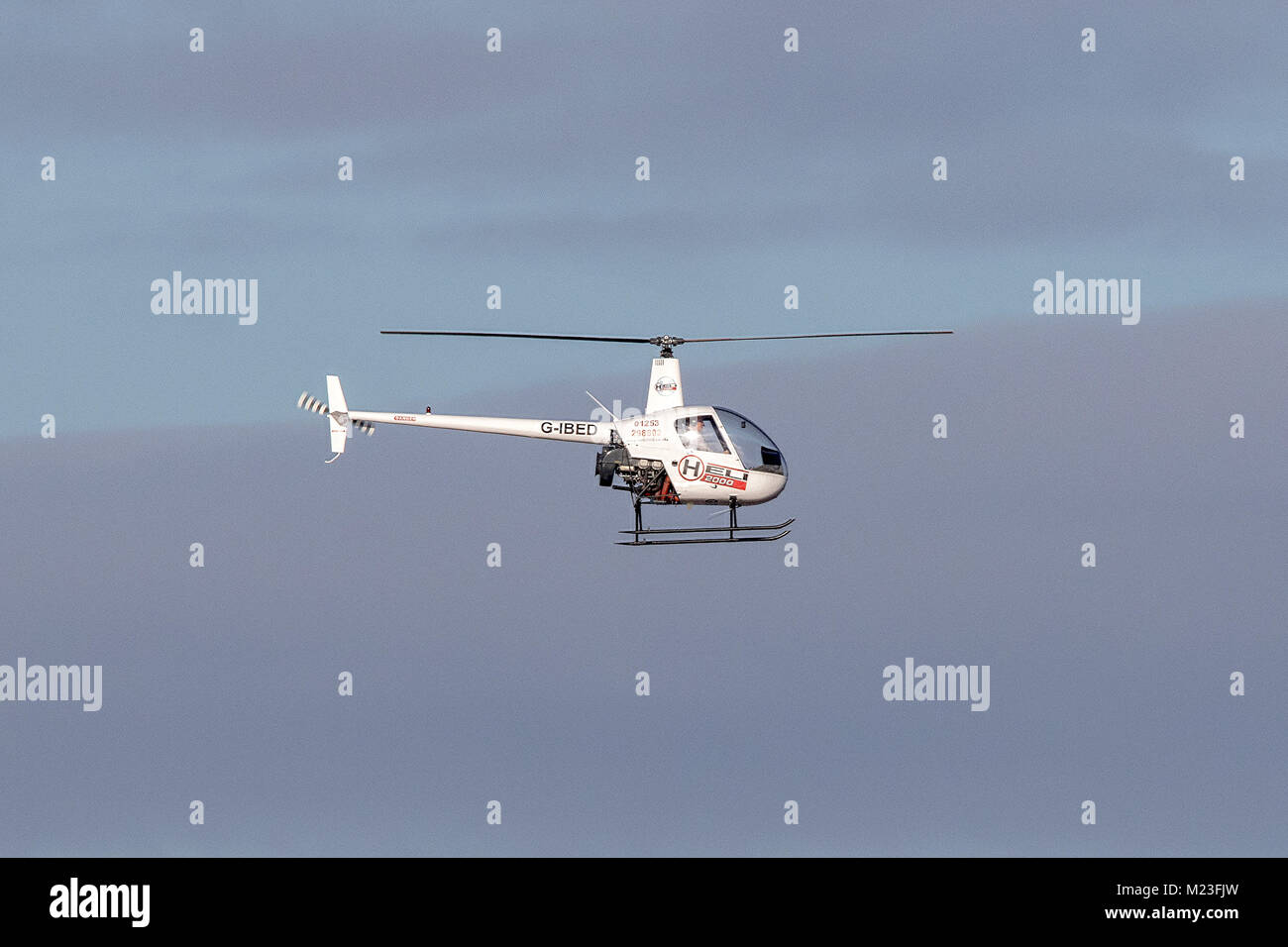 A Robinson R-22 Beta II, 2 seater piston powered helicopter landing on Southport beach in Merseyside, UK. - Stock Image