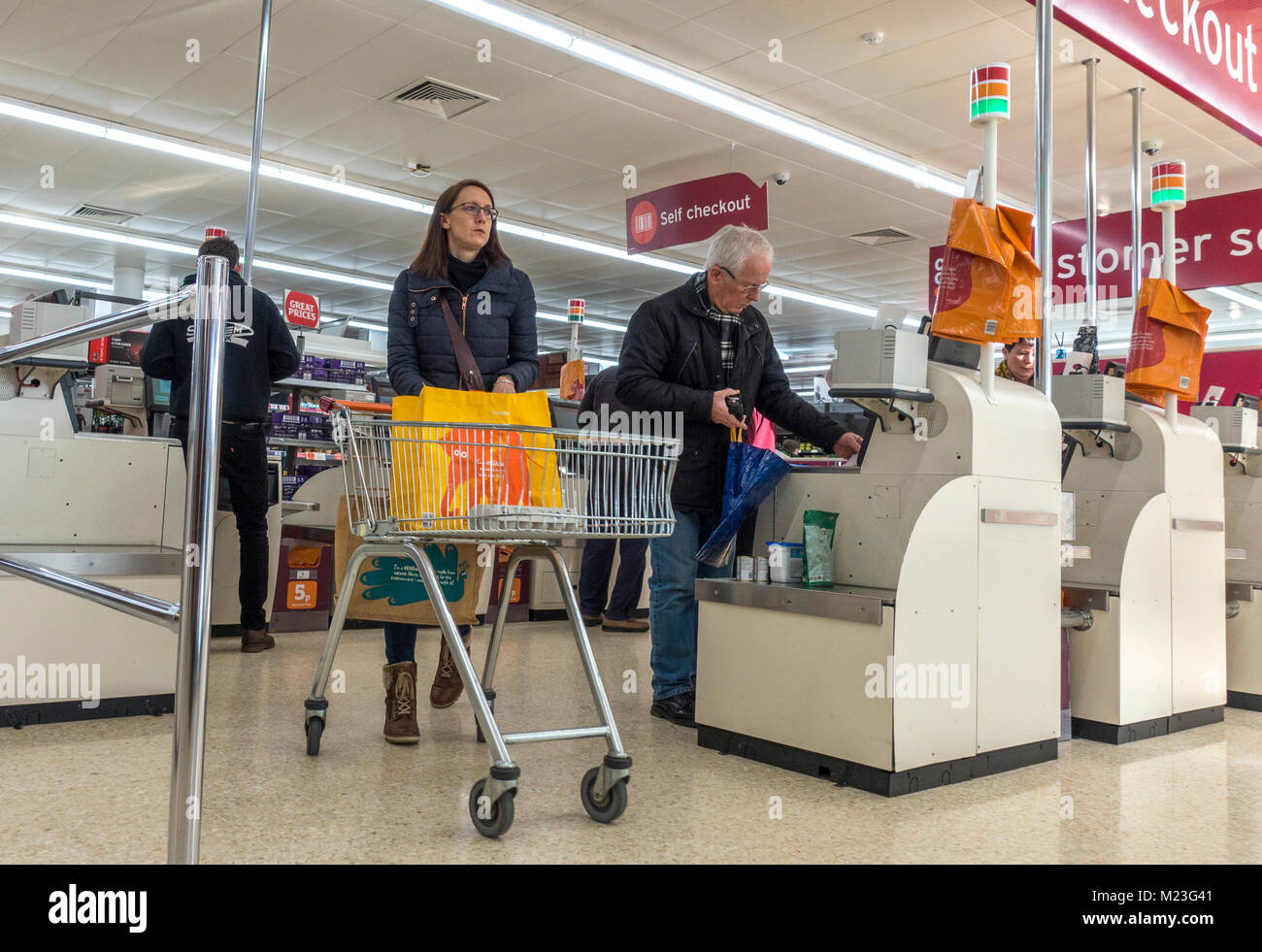 Woman with trolley and customers paying for their shopping at the self checkout area of Sainsbury's supermarket - Stock Image