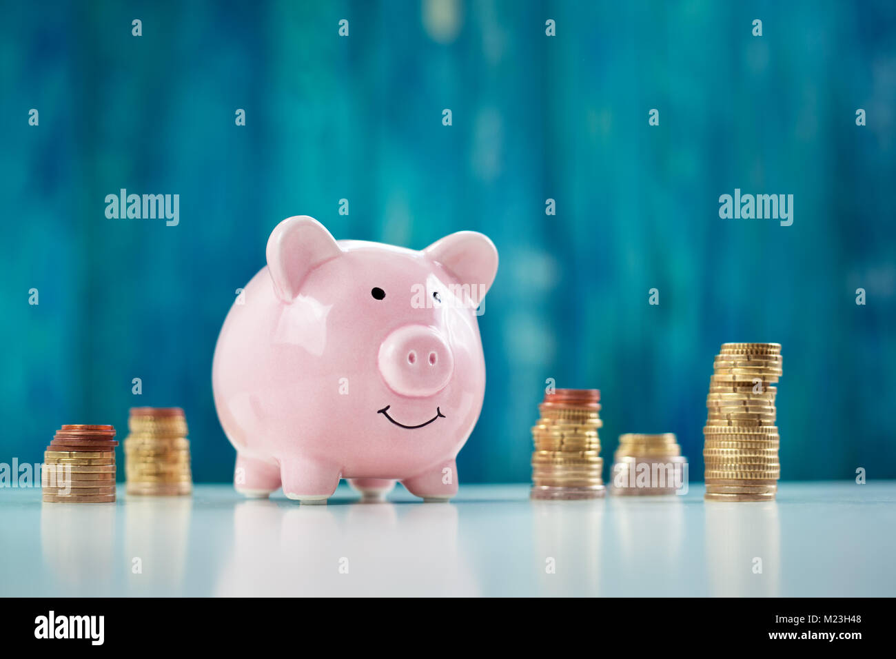 piggy bank with stacked coins - Stock Image