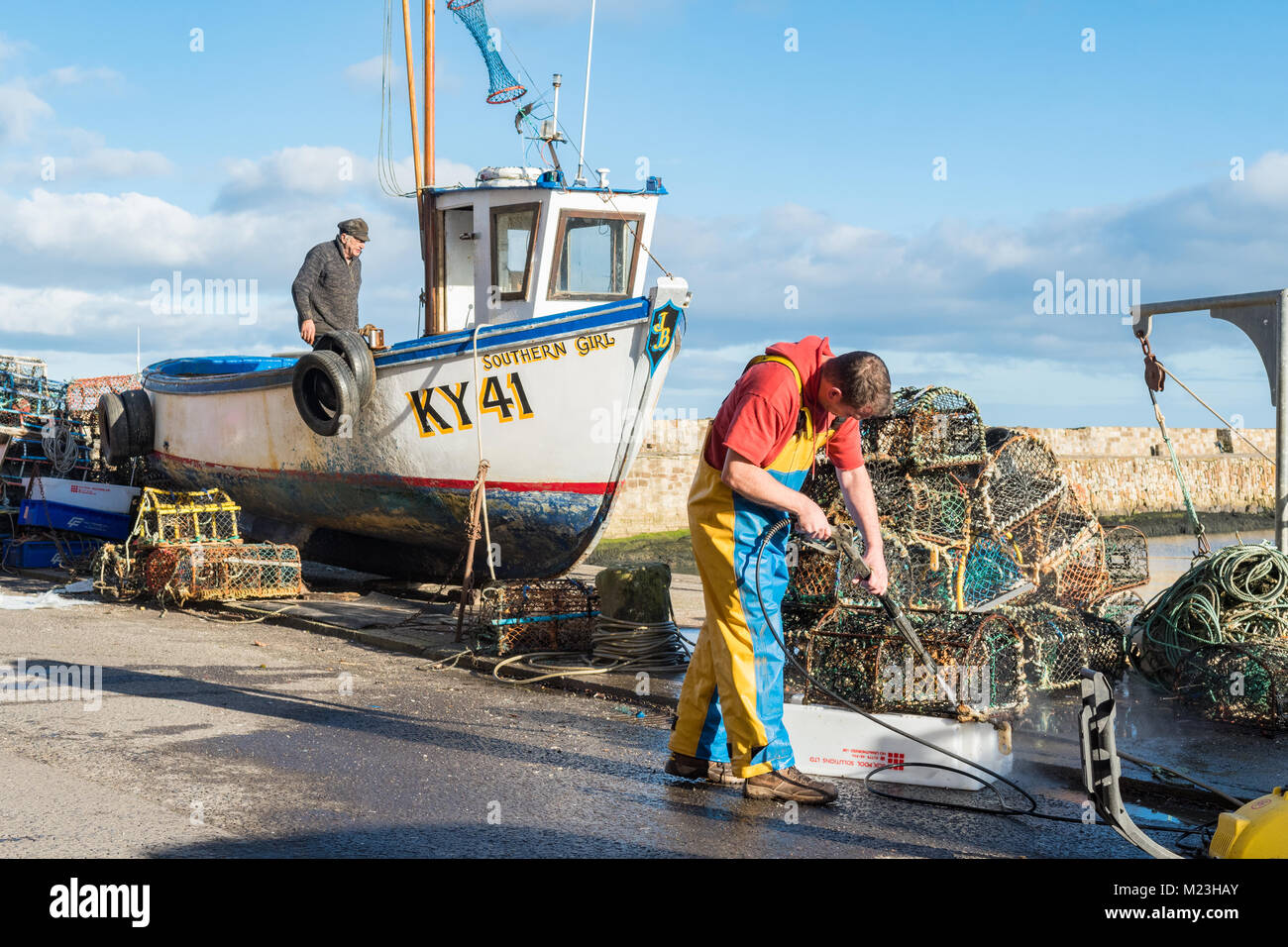 Fisherman cleaning lobster pots and small potter fishing boat at St Andrews Harbour, St Andrews, Scotland, UK - Stock Image