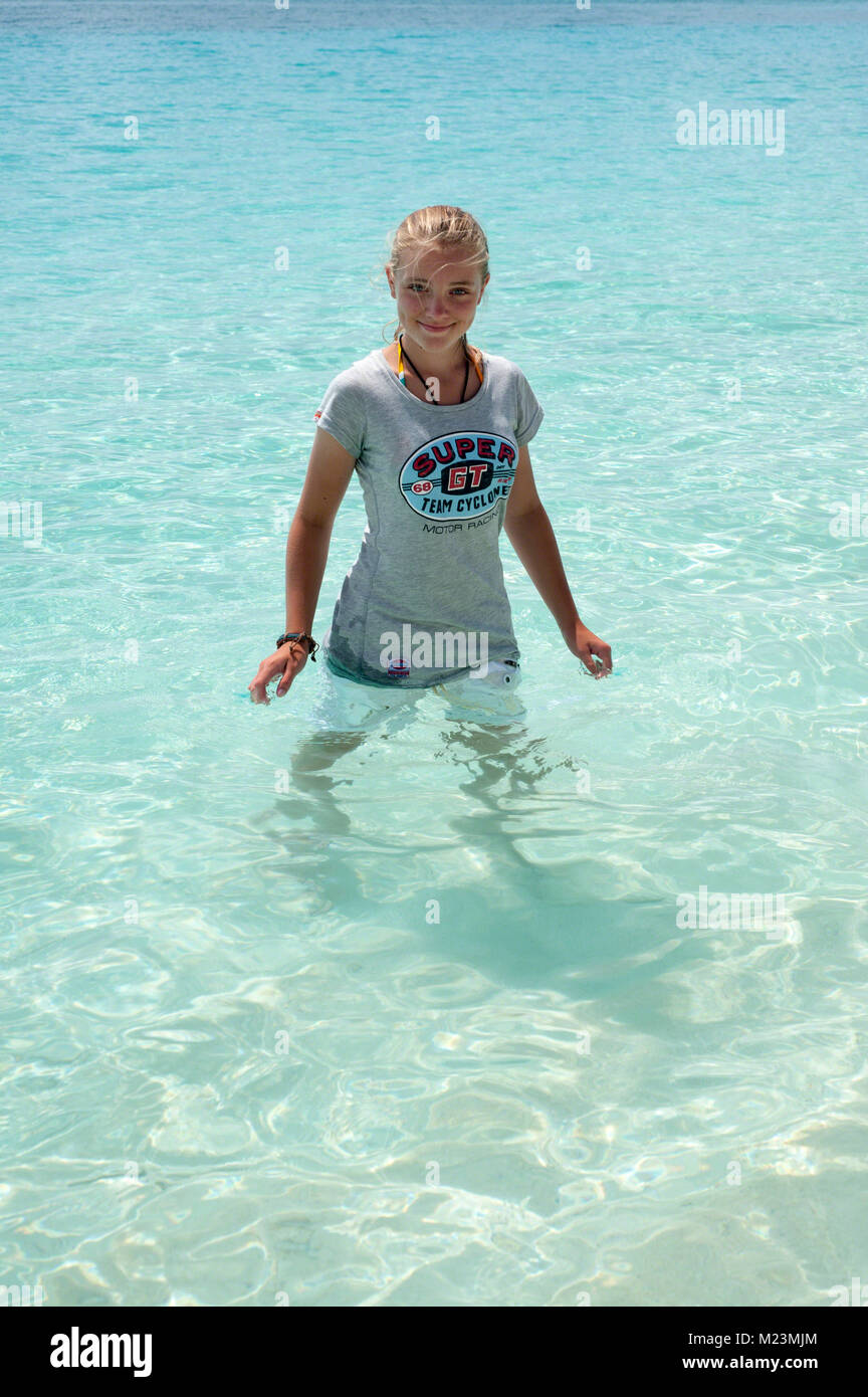 Cooling down in the crystal clear tropical waters on Seven Mile Beach, Grand Cayman. - Stock Image