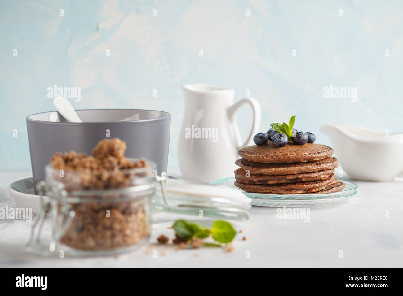 Chocolate pancakes, chocolate baked granola in a jar and milk. Healthy breakfast concept. Stock Photo