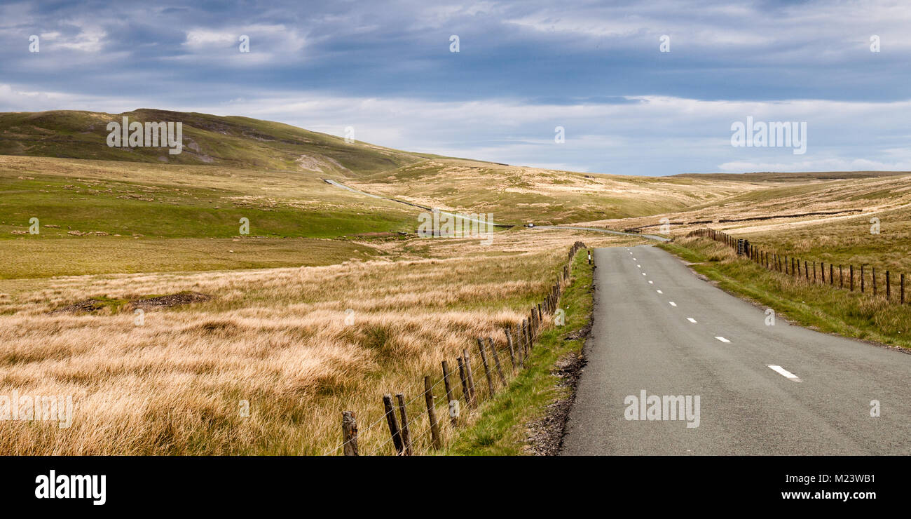 The B6276 road winds across desolate open moorland in the North Pennines hills of North Yorkshire, England. - Stock Image