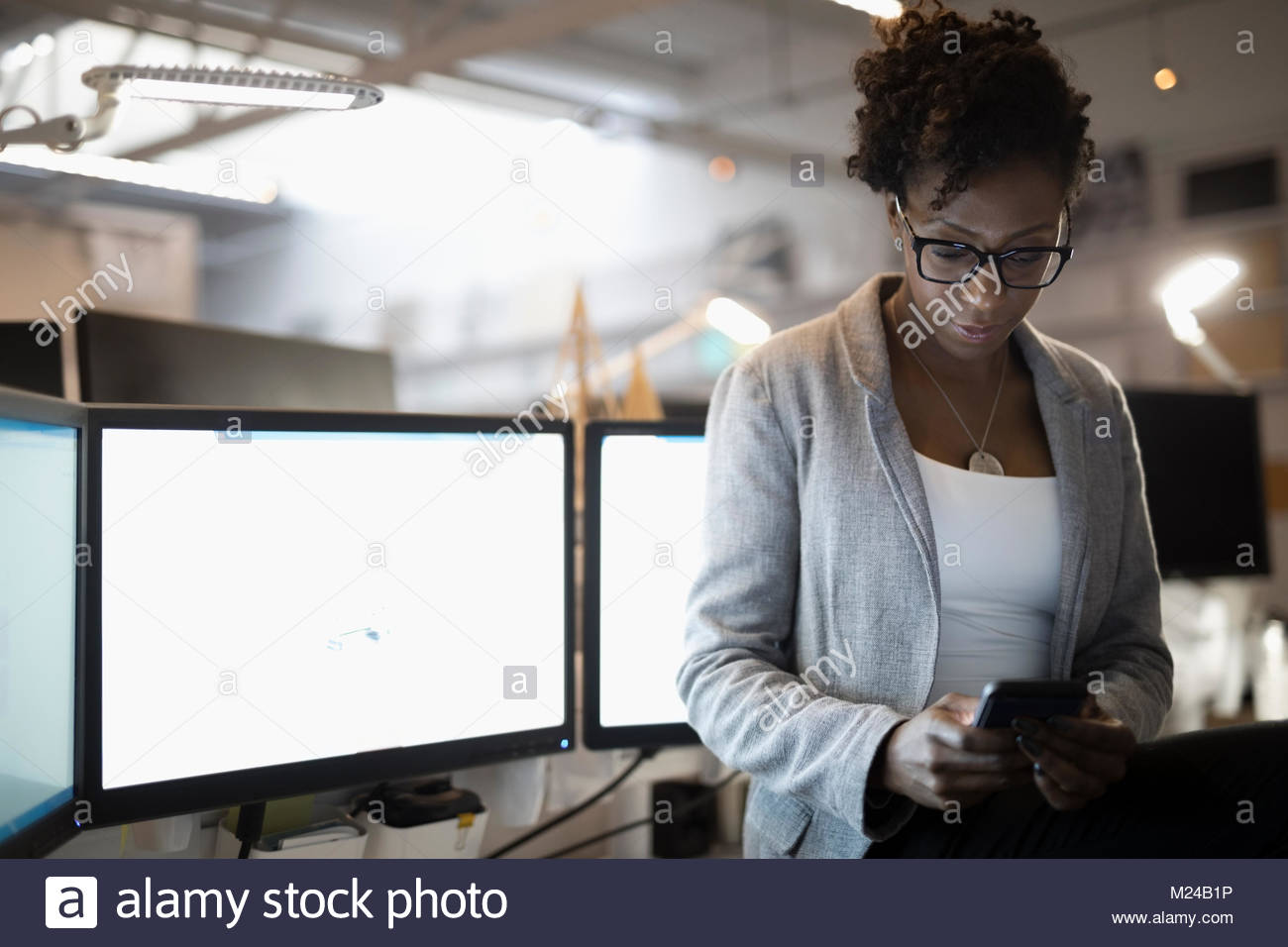 Dedicated businesswoman using smart phone at computers in office - Stock Image