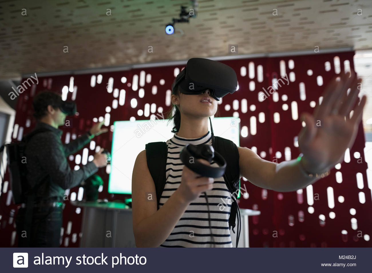 Computer programmer testing virtual reality simulator glasses and joysticks in office - Stock Image