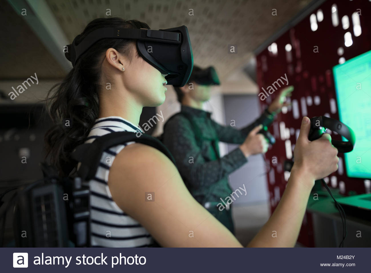 Computer programmers testing virtual reality simulator glasses and joysticks in office - Stock Image