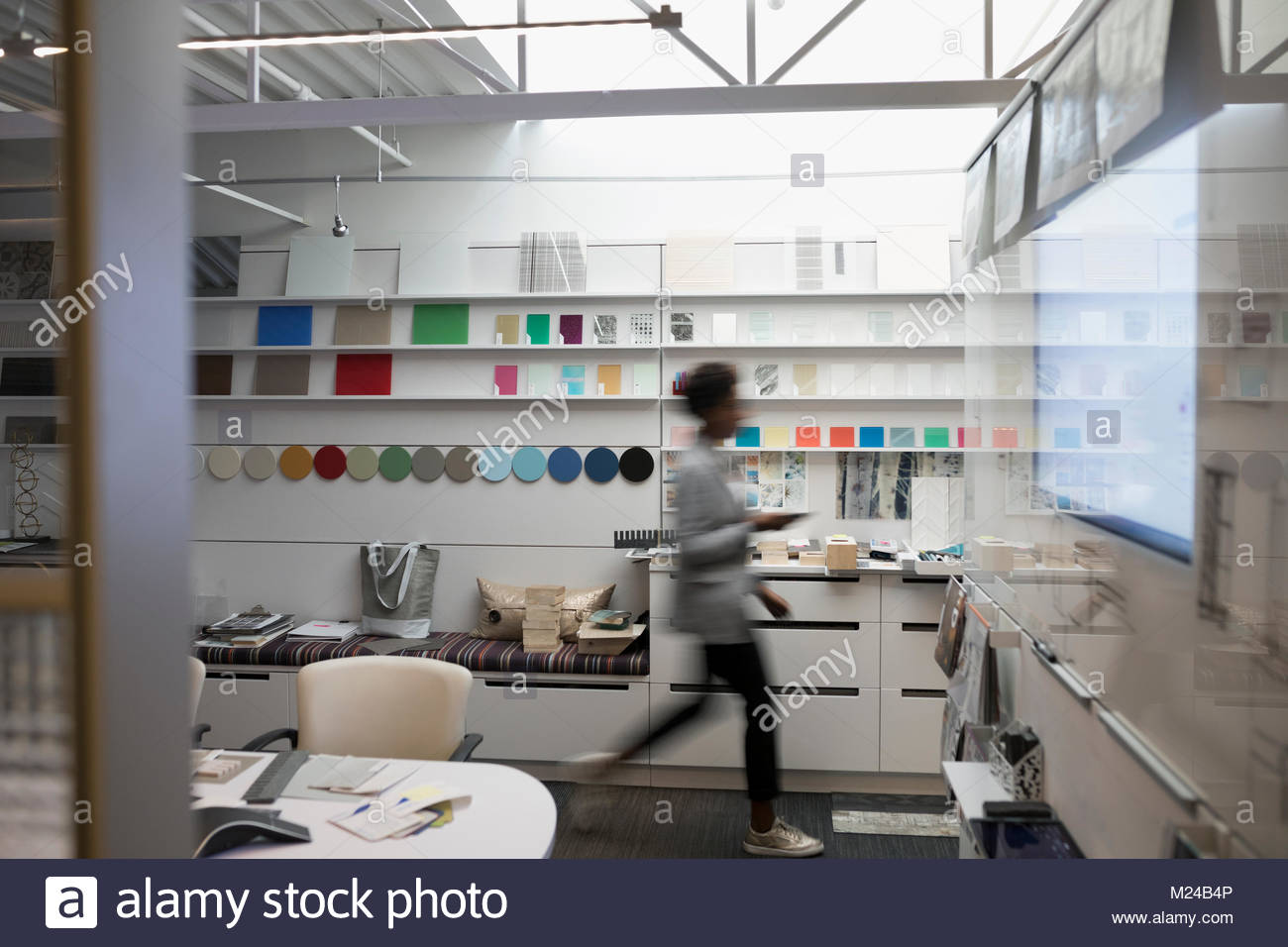 Designer walking past color swatches in creative office - Stock Image