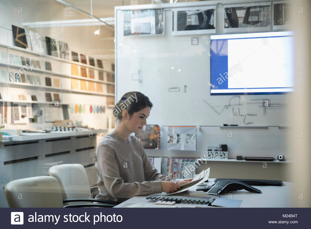 Designer viewing swatches, planning in creative office - Stock Image