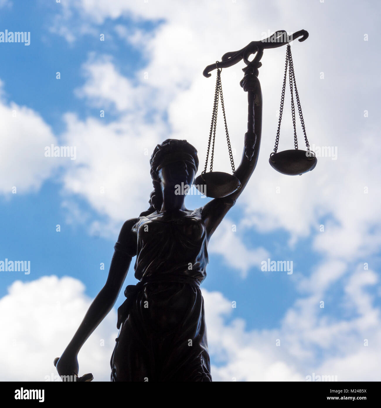 Statue of Justice with scales against the sky and clouds. Legal law, advice and justice concept - Stock Image