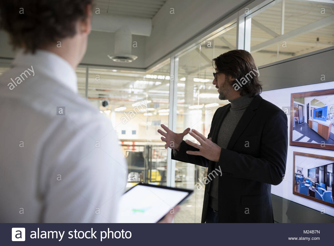 Architect leading meeting at screen in office - Stock Image