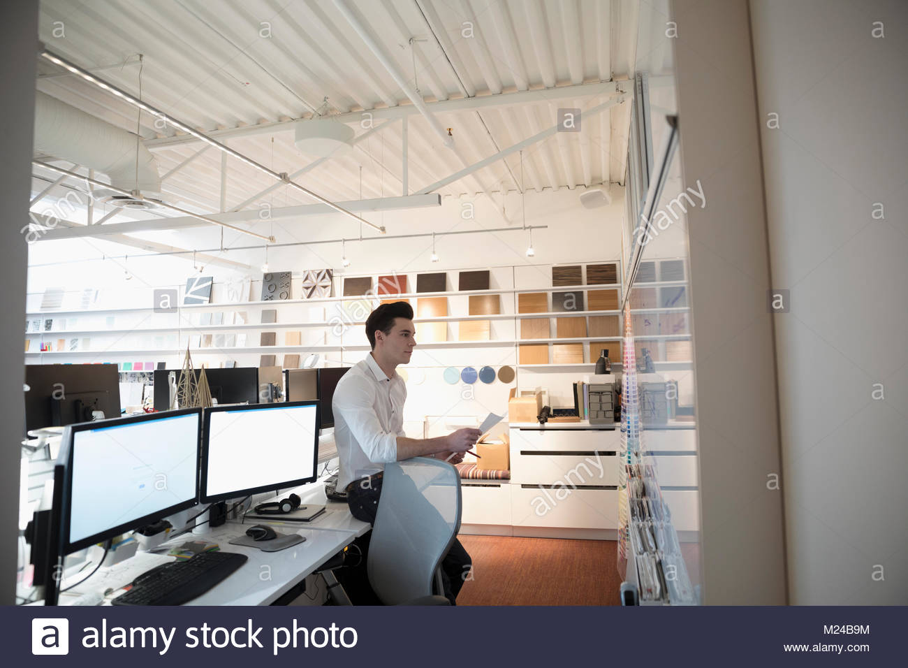Designer brainstorming at whiteboard in creative office - Stock Image