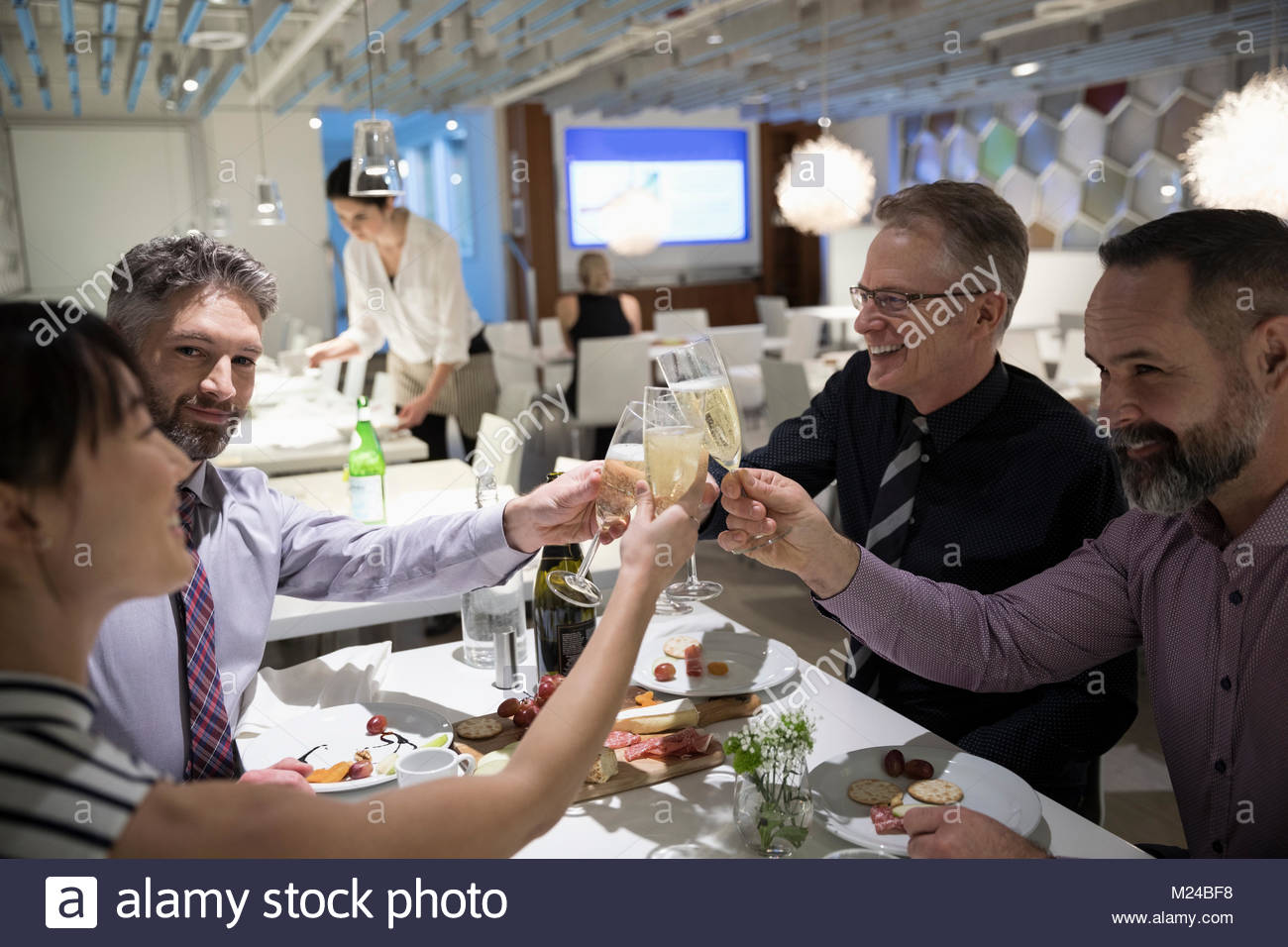 Business people celebrating, toasting champagne glasses at restaurant table - Stock Image
