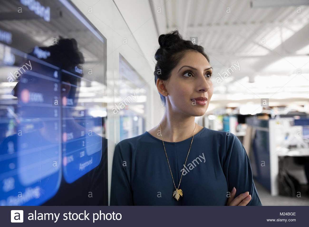 Determined businesswoman at screen in office - Stock Image