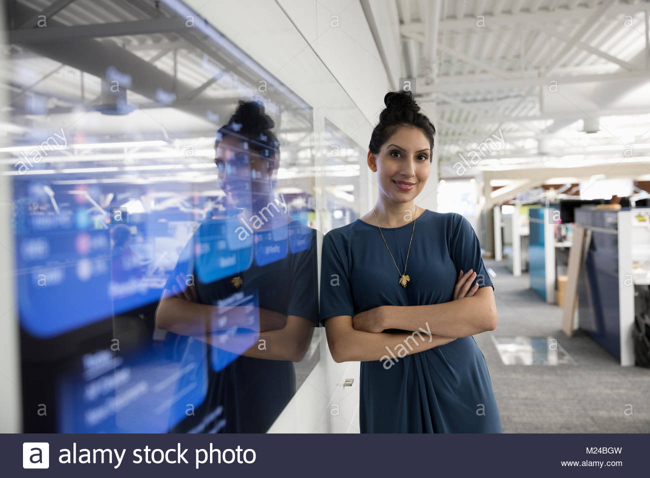 Portrait confident businesswoman at screen in office - Stock Image