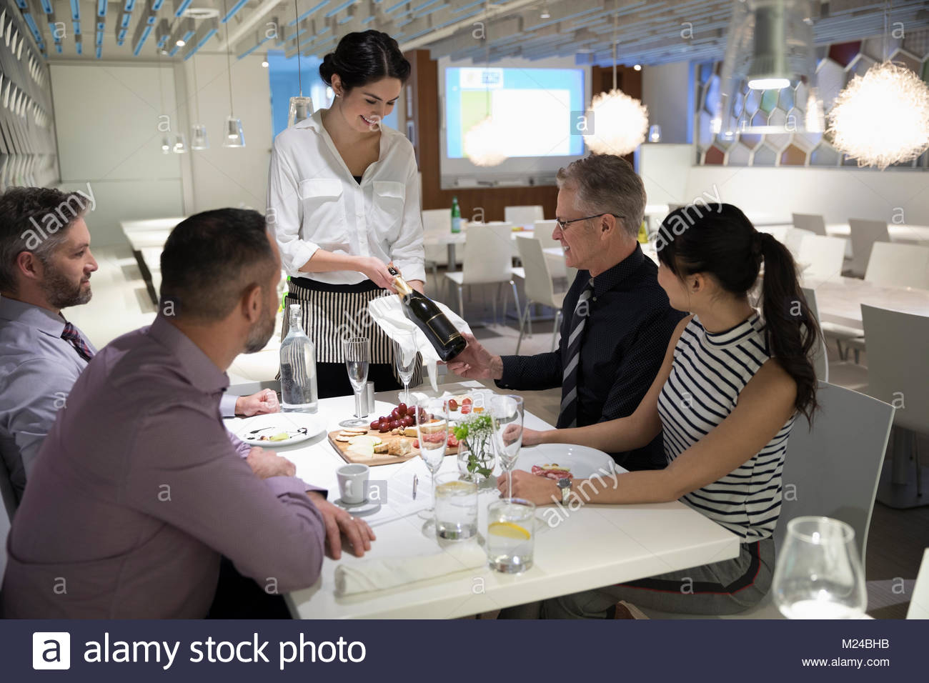 Waitress presenting bottle of champagne to business people at restaurant table - Stock Image