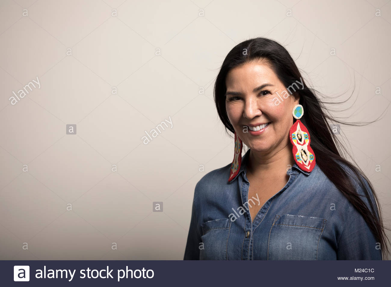 Portrait smiling, confident mature Native American woman with colorful earrings - Stock Image