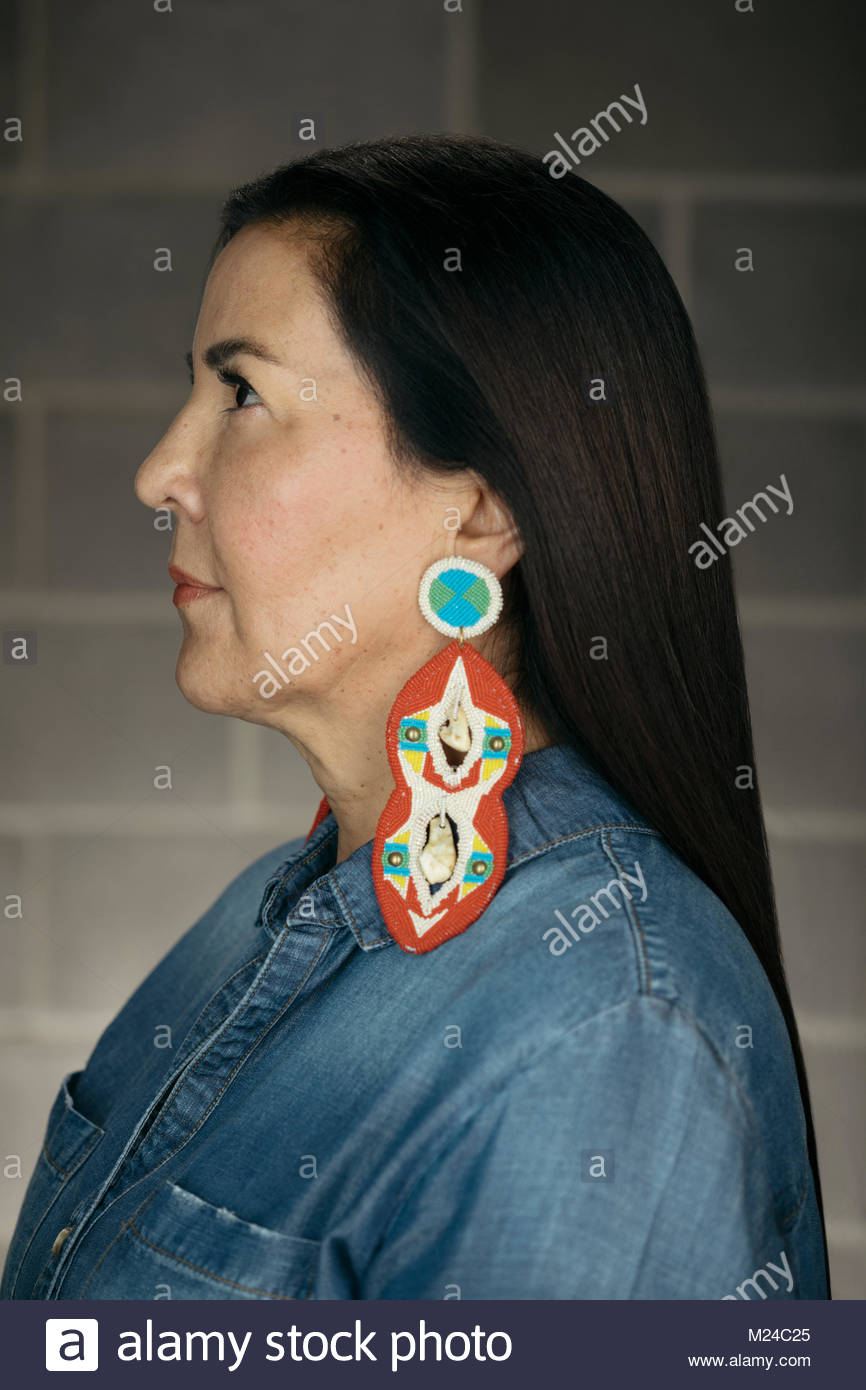 Profile confident mature Native American woman with colorful earrings - Stock Image