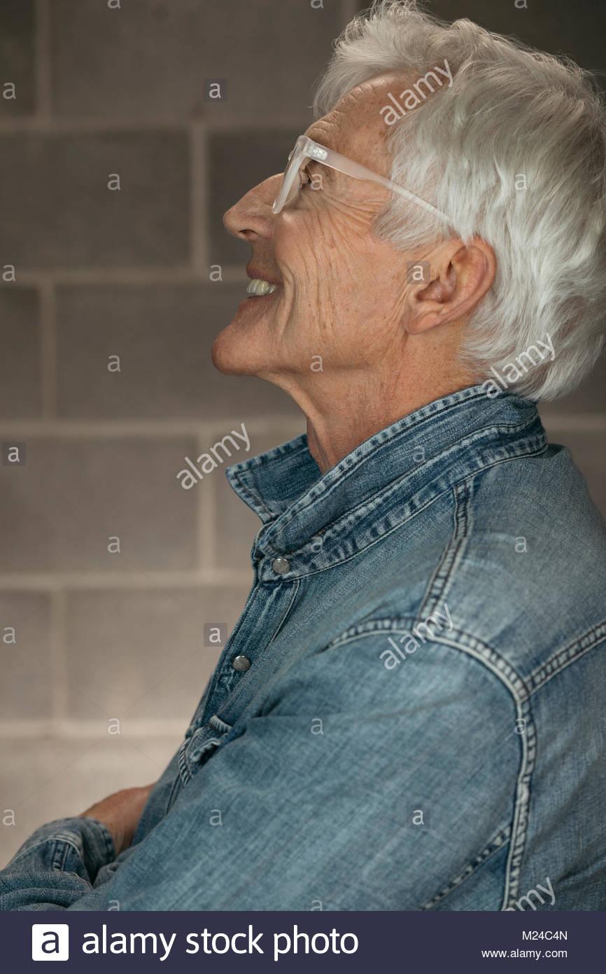 Profile carefree, happy senior man in denim shirt - Stock Image