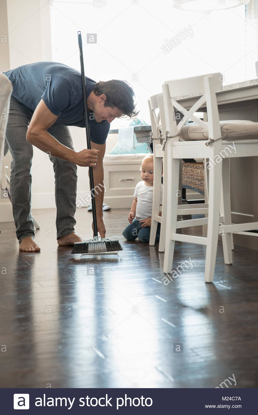 Baby son watching father sweeping floor - Stock Image