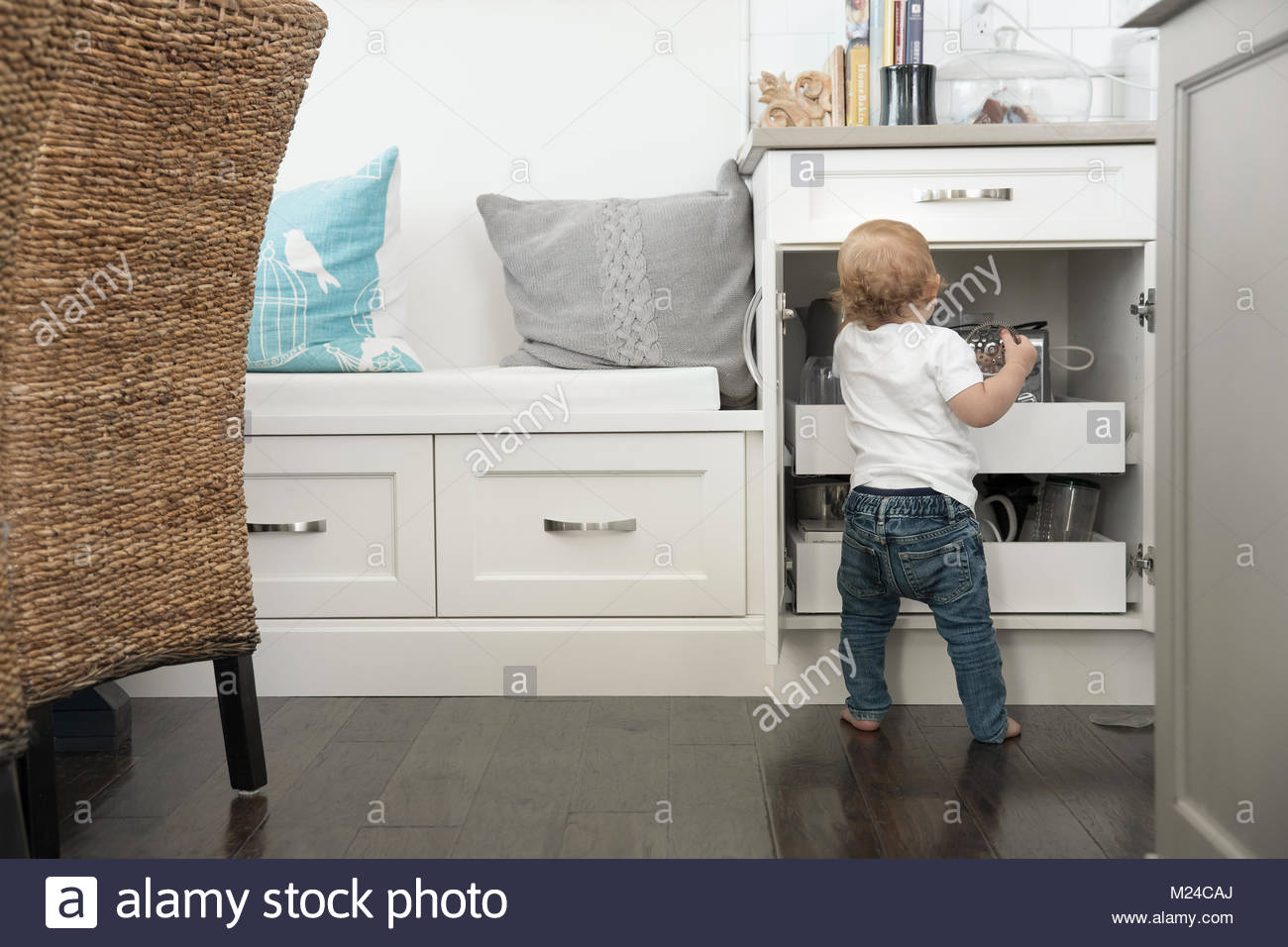 Curious baby boy reaching in kitchen cupboard - Stock Image