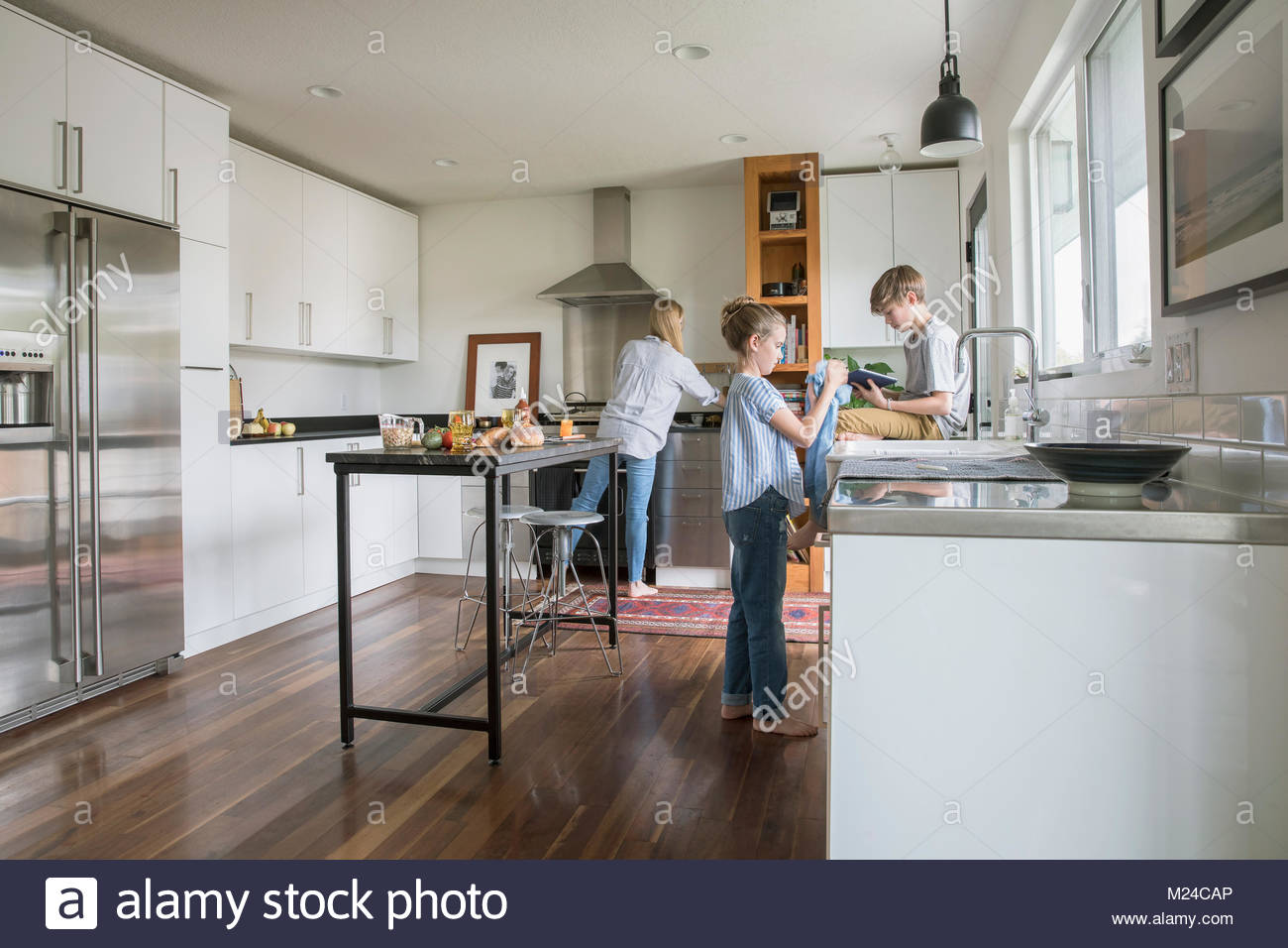 Family cooking and doing dishes in kitchen - Stock Image