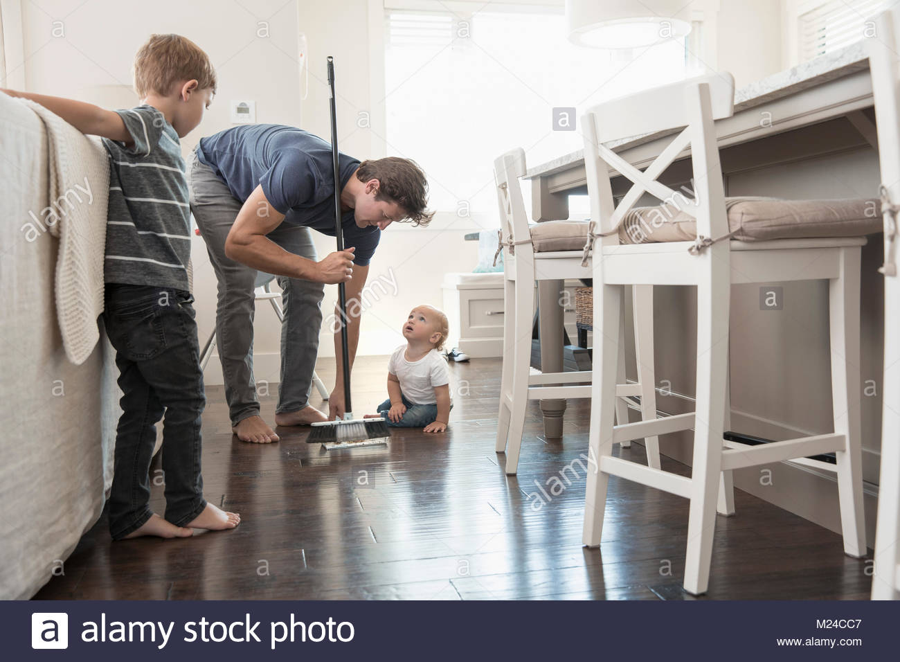 Sons watching father sweeping floor - Stock Image