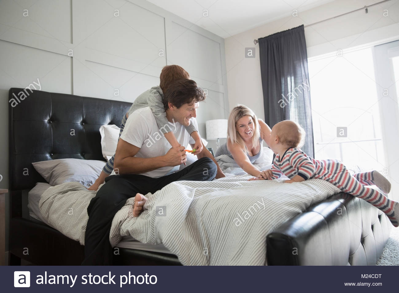 Playful family on bed Stock Photo