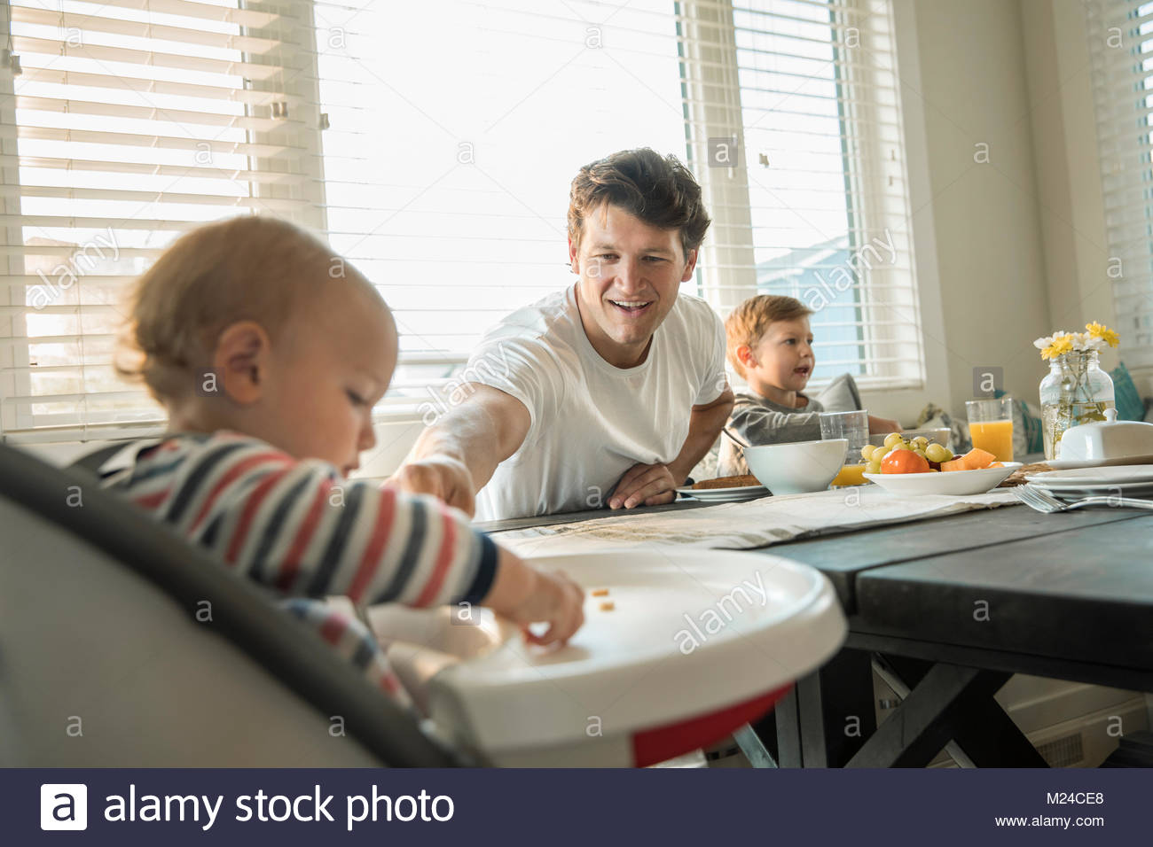 Father feeding baby son in high chair - Stock Image