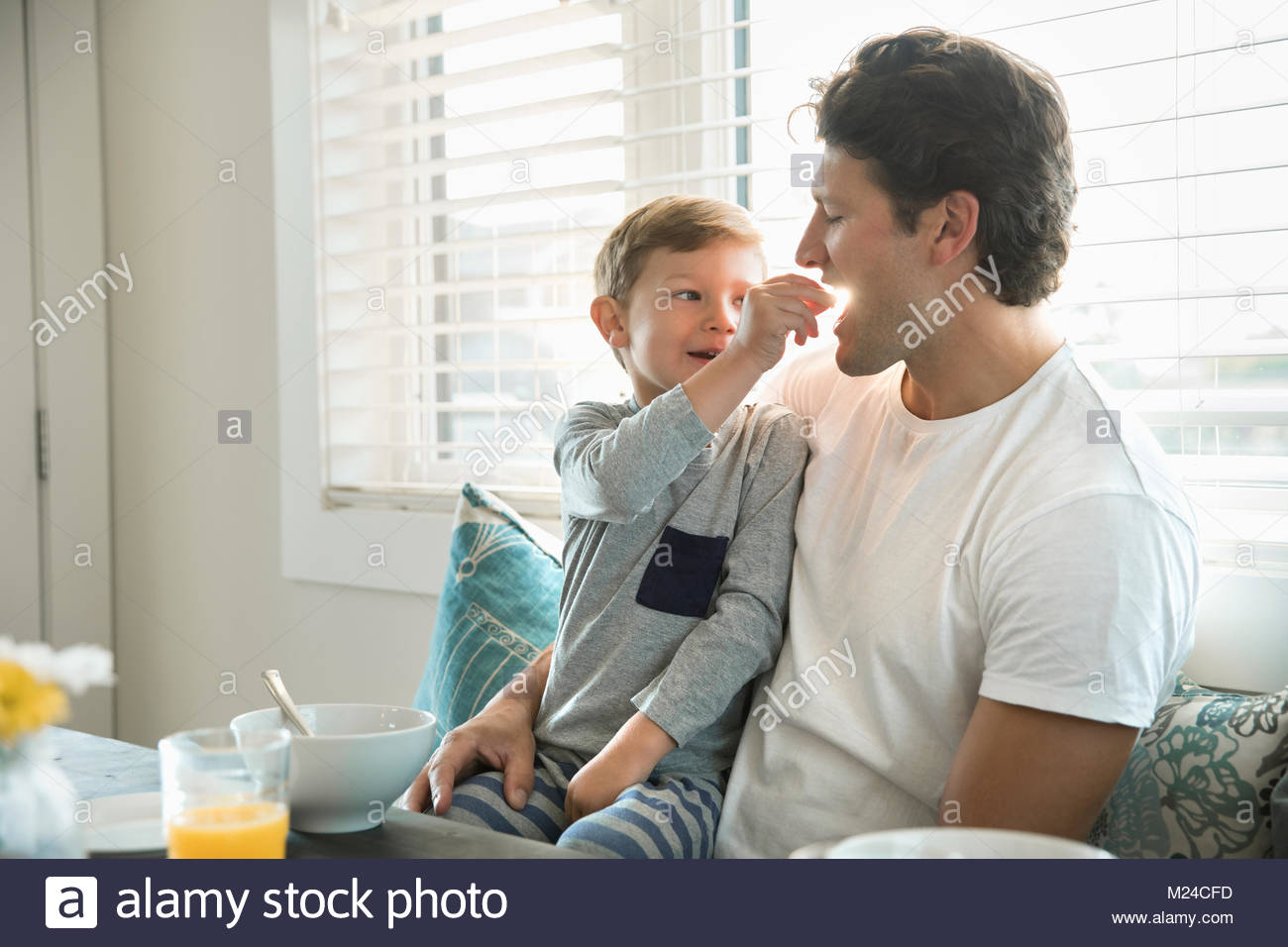 Son feeding cereal to father in breakfast nook - Stock Image
